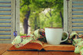 Romantic scene of cup of coffee next to old book in front of cou Royalty Free Stock Photo
