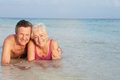 Romantic senior couple lying in sea on beach holiday smiling to camera Stock Photography