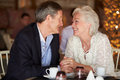 Romantic senior couple in restaurant enjoying cup of coffee smiling to each other Royalty Free Stock Photo