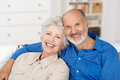 Romantic senior couple sitting close together on a sofa in the house smiling happily at the camera Stock Photo