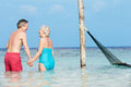 Romantic senior couple standing in beautiful tropical sea holding hands Stock Image