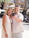Romantic senior mature couple taking selfie photo on vacation middle aged posing for a their mobile phone with palms in background Stock Image