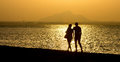 Romantic stroll along the beach at sunset couple a b c Royalty Free Stock Photo
