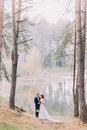 Romantic stroll of newlywed couple on the forest lake sandy shore Royalty Free Stock Photo