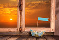 Romantic sunset view out of the window background with boat fo holiday dreams wooden to decorated a sail on windowsill Royalty Free Stock Photography