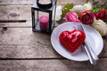 Romantic table setting.  Decorative red heart, knife and fork on white plate Royalty Free Stock Photo
