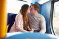 Romantic teenage couple kissing on bus happy Stock Photos