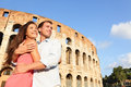 Romantic travel couple in rome by coliseum embracing italy happy lovers on honeymoon sightseeing having fun front of Royalty Free Stock Photos