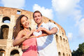 Romantic travel couple in rome by colosseum italy happy lovers on honeymoon showing heart sharped hands having fun front of Stock Photo