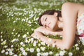 Romantic woman day dreaming happy resting and lying down on grass and daisies in park outdoors beautiful girl with closed eyes in Royalty Free Stock Photography