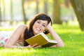 Romantic woman reading book in summer happy lying down on grass park brunette beautiful girl relaxing and enjoying leisure on Stock Image