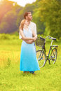 Romantic young caucasian couple having romantic time together in the park with bicycle vertical image Royalty Free Stock Images