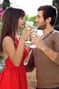 Romantic young couple dancing with glasses of white wine in their hands as they stare into each others eyes with a smile Royalty Free Stock Images