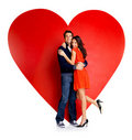 Romantic young couple embracing against red heart Stock Image