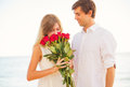 Romantic young couple in love man giving beautiful young woman women red roses Stock Image