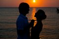 Romantic young couple sunset silhouette on beach. Stock Images