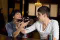 Romantic young couple toasting with red wine entwining their arms as they celebrate together while seated at a bar counter in a Stock Photo