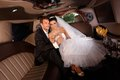Romantic young couple on wedding day sitting in limo clinking glasses Stock Images