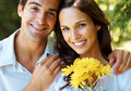 Romantic young couple with yellow flowers smiling Royalty Free Stock Images