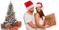 Romantic young man giving his wife an xmas gift men holding her in a close embrace as she smiles at him with a large present Stock Photography