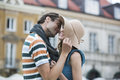 Romantic young man kissing woman against buildings men women Royalty Free Stock Photo