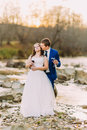 Romantic young newlywed pair drinking red wine on pebble river bank with forest hills and stream Royalty Free Stock Photo