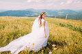 Romantic young pretty bride posing on the windy golden autumn field with small flowers. Hill landscape at background Royalty Free Stock Photo