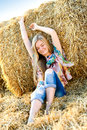Romantic young woman posing outdoor field with hay Stock Photo