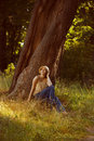 Romantic young woman sitting under a tree big Royalty Free Stock Photos