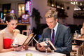 Romantically dinner young happy couple dining out in restaurant and reading menu Royalty Free Stock Photos