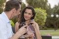 Romantyczne potomstwo pary mienia ręki podczas gdy mieć czerwone wino w parku Obrazy Royalty Free