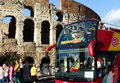 Rome city sightseeing double decker touristic red bus at the colosseum or coliseum colosseum originally the flavian amphitheatre Royalty Free Stock Images