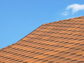 Roof of bituminous tiles taken closeup against blue sky Royalty Free Stock Images