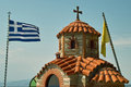 The roof of the chapel with greek flag with a beautiful blue sky over mediterranean sea in port ourinopoli Royalty Free Stock Photography