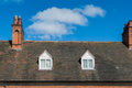 Roof chimney on a tiled with blue sky and clouds in background Royalty Free Stock Image