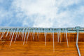 Roof of the house with hanging icicles edge on blue sky background Stock Photography