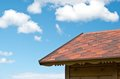 Roof and the sky with clouds edge of of a wooden house on a background of blue Stock Photo