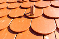 Roof tiles shaped in the form of a beaver tail detail red with snow guards Stock Photos