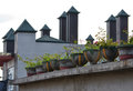 Roof top pots on a rooftop with triangle chimney Royalty Free Stock Photo