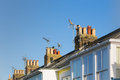 Roof tops with chimneys and TV aerials on terrace, row houses. Royalty Free Stock Photo