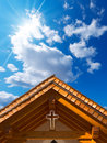 Roof of wooden church with cross small chapel a and blue sky clouds and sun rays Royalty Free Stock Image