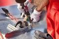 Roofer builder worker finishing folding a metal sheet using metal shears. Royalty Free Stock Photo