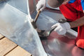 Roofer builder worker finishing folding a metal sheet using rubber mallet. Royalty Free Stock Photo