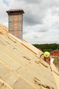 Roofer builder worker installing roof insulation material rockwool on new house under construction. Royalty Free Stock Photo
