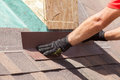Roofer builder worker installing shingles on a new wooden roof with skylight. Royalty Free Stock Photo