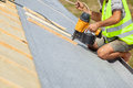 Roofer builder worker use automatic nailgun to attach roofing membrane. Royalty Free Stock Photo