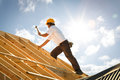 Roofer carpenter working on roof on construction site Royalty Free Stock Photo
