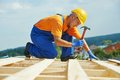 Roofer carpenter works on roof construction worker nailing wood board with hammer installation work Royalty Free Stock Photo