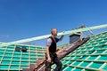 Roofer che scala il tetto con un fascio Fotografia Stock
