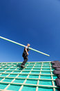 Roofer climbing the roof with a beam low angle view of in direction of assembly point Royalty Free Stock Images